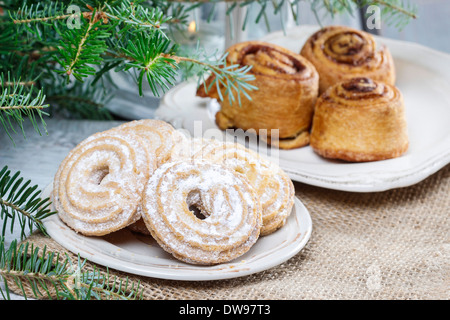 Round cookies on christmas eve tableRound cookies and cinnamon rolls on christmas eve table - Stock Photo