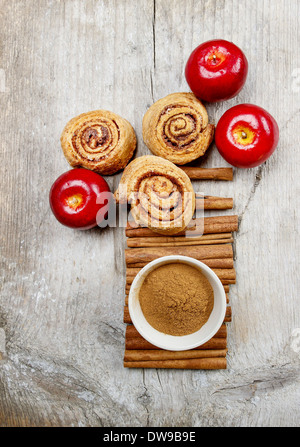 Bowl of cinnamon and cinnamon buns on wooden tableBowl of cinnamon and cinnamon buns on wooden table - Stock Photo