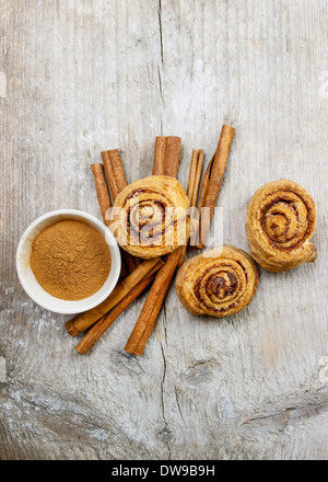 Bowl of cinnamon and cinnamon buns on wooden tableBowl of cinnamon and cinnamon buns on wooden table - Stockfoto