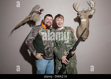 Home portrait of father and teenage son holding shotgun - Stock Photo