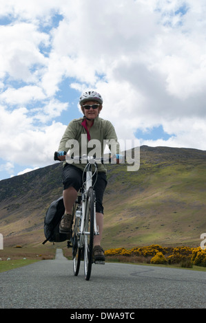 A female cyclist on Mungrisedale narrow road in the English Lake District on a sunny Spring day. - Stock Photo