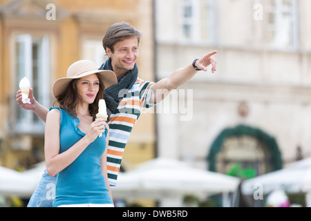 Young couple enjoying ice cream cones during vacation - Stock Photo