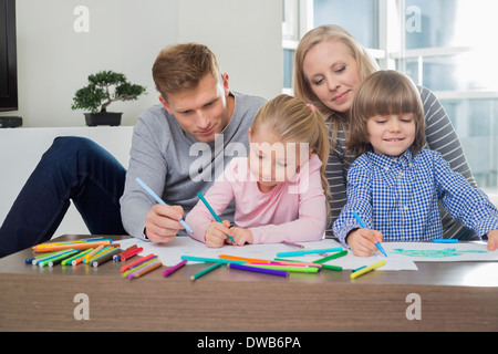 Mid adult parents with children drawing together at home - Stock Photo