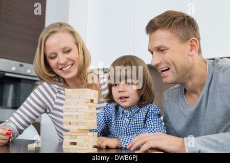 Happy parents and son playing with wooden blocks at home - Stock Photo