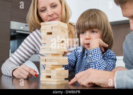 Family playing with wooden blocks at home - Stock Photo