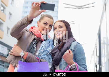 Female friends with shopping bags taking photos through mobile phone - Stock Photo