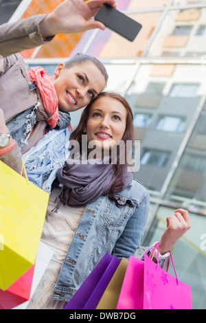Women with shopping bags taking self portrait through mobile phone - Stock Photo