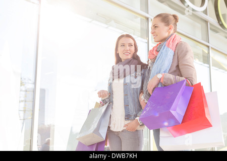 Young women carrying shopping bags by store - Stock Photo