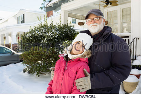 Grandfather and granddaughter outside house in winter - Stock Photo