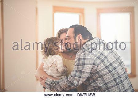 Parents and toddler daughter enjoying group hug at home - Stock Photo