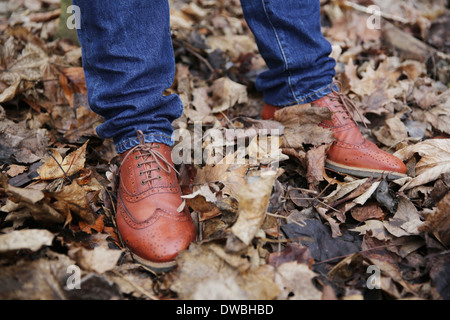 Precious leather shoes of man standing in the wood - Stock Photo