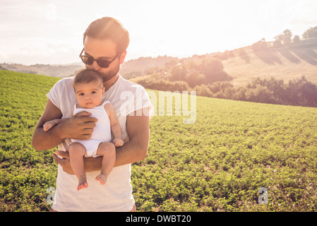 Portrait of proud father holding up baby daughter - Stock Photo