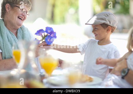 Boy giving flowers to grandmother - Stock Photo