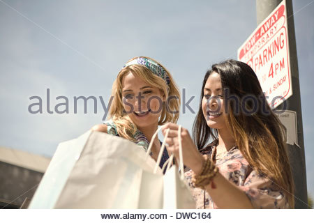 Two young women on street looking in shopping bags - Stock Photo