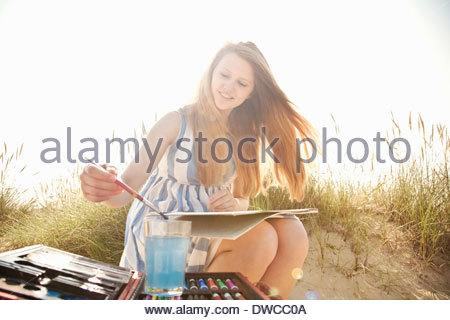 Teenage girl drawing on the beach - Stock Photo