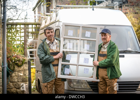 Portrait of father and son builders holding new window - Stock Photo