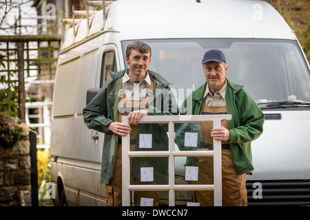 Portrait of father and son builders holding new window for installation - Stock Photo