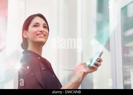 Young businesswoman holding smartphone with lights coming out of it - Stock Photo