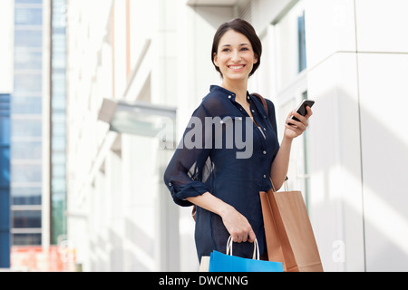 Young businesswoman carrying smartphone and shopping bags - Stock Photo