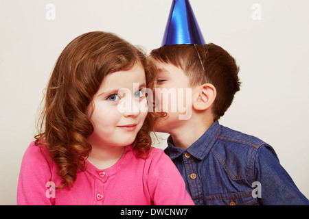 Boy wearing party hat whispering to girl - Stock Photo