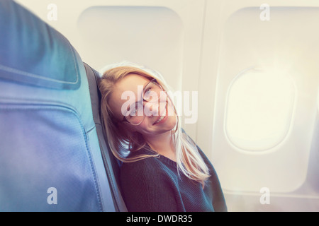 Smiling young woman in airplane, portrait - Stock Photo