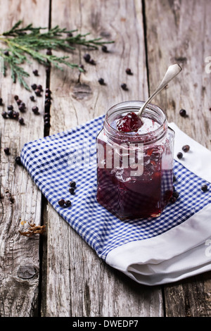 Jar of plum and juniper jam on old wooden table - Stock Photo