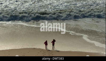 Two children standing on the beach in coats and wellies - Stock Photo