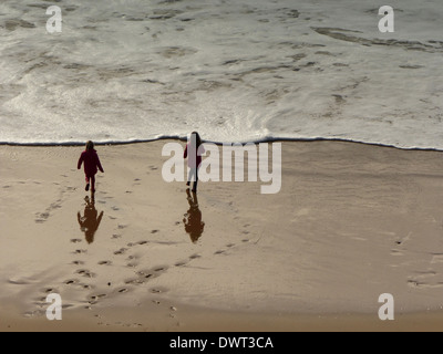 Two children playing in the sea in coats and wellies - Stock Photo