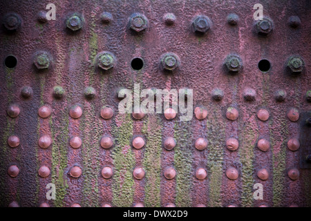 Detail of a grungy, faded, red plate on the side of an old rusting steam engine in England, UK - Stock Photo