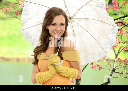 Portrait of young woman in Victorian dress holding umbrella outdoors - Stock Photo