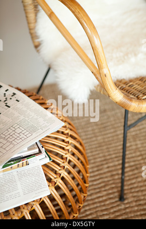Crossword puzzle on bamboo table next to chair, high angle view - Stock Photo