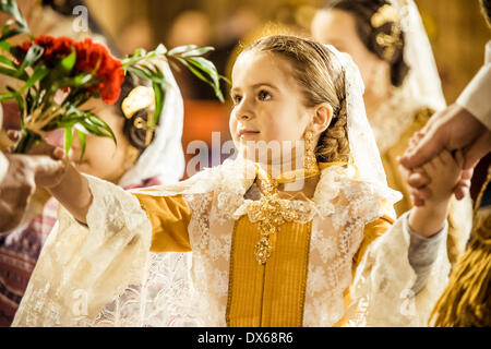 Valencia, Spain. March 18th, 2014: A little Fallera finally offers her flower bouquet to the Virgin and hands it - Stock Photo