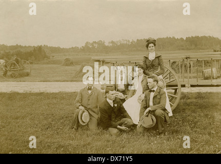 Circa 1900 antique photograph, three young couples by a haywagon in a field. Probably New England, USA. - Stock Photo