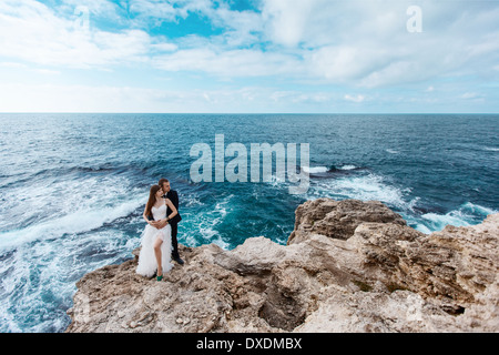 Bride and groom near the ocean - Stock Photo