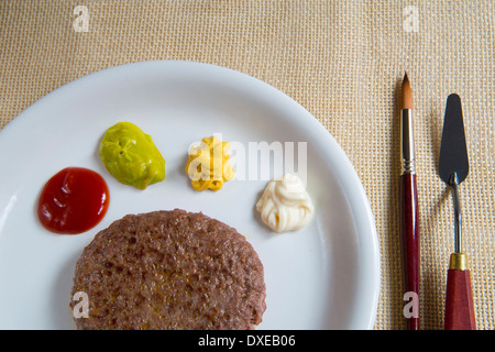 Artistic cuisine: hamburger and palette of assorted sauces, served with paint brush and palette knife as fork and - Stock Photo