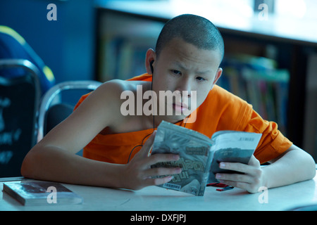 Young Monk reading a book while listening to music - Stock Photo