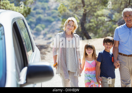 Grandparents and grandchildren holding hands outside car - Stock Photo