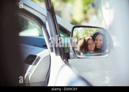 Reflection of smiling mother and daughter in side-view mirror - Stock Photo