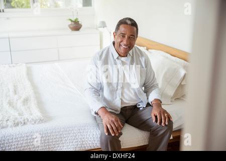 Portrait of smiling senior man sitting on bed - Stock Photo