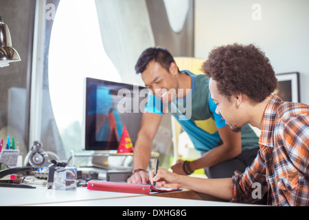 Casual businessmen reviewing paperwork in office - Stock Photo