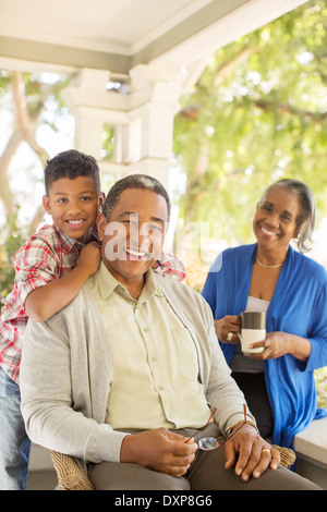 Portrait of smiling grandparents and grandson on porch - Stock Photo