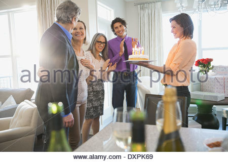 Family and friends celebrating womans birthday at home - Stock Photo