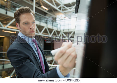 Businessman writing on whiteboard in office atrium - Stock Photo