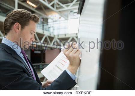 Businessman writing on whiteboard in office - Stock Photo