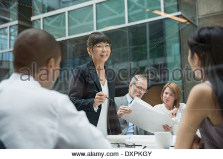 Businesswoman leading meeting in conference room - Stock Photo