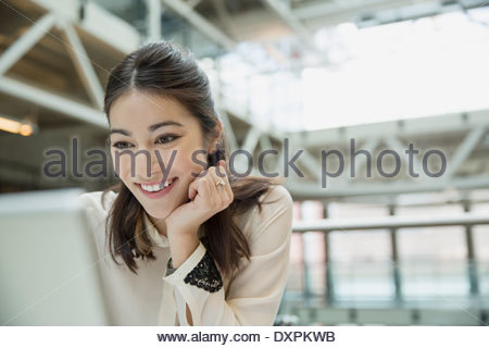 Happy businesswoman using laptop - Stock Photo