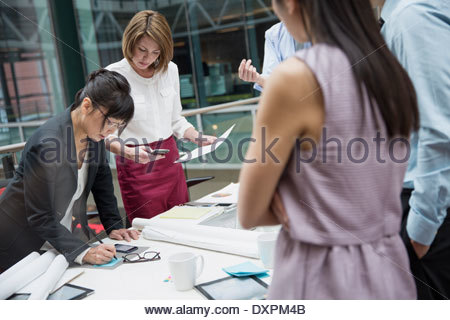 Business people standing around conference table in meeting - Stock Photo
