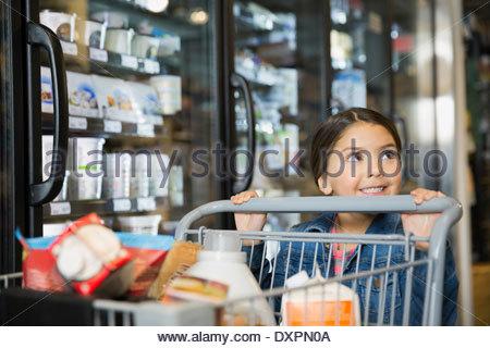 Girl pushing shopping cart in market - Stock Photo
