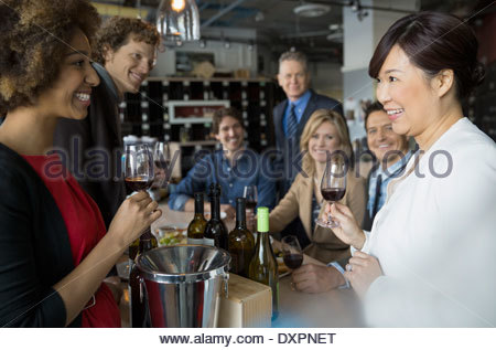 Sommelier and couples wine tasting in store - Stock Photo