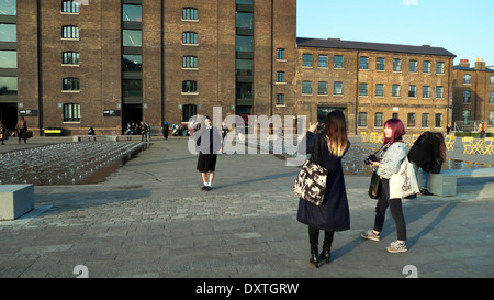 Asian students photographing friend outside UAL CSM Central St Martins, Granary Square, Kings Cross London N1  KATHY - Stock Photo